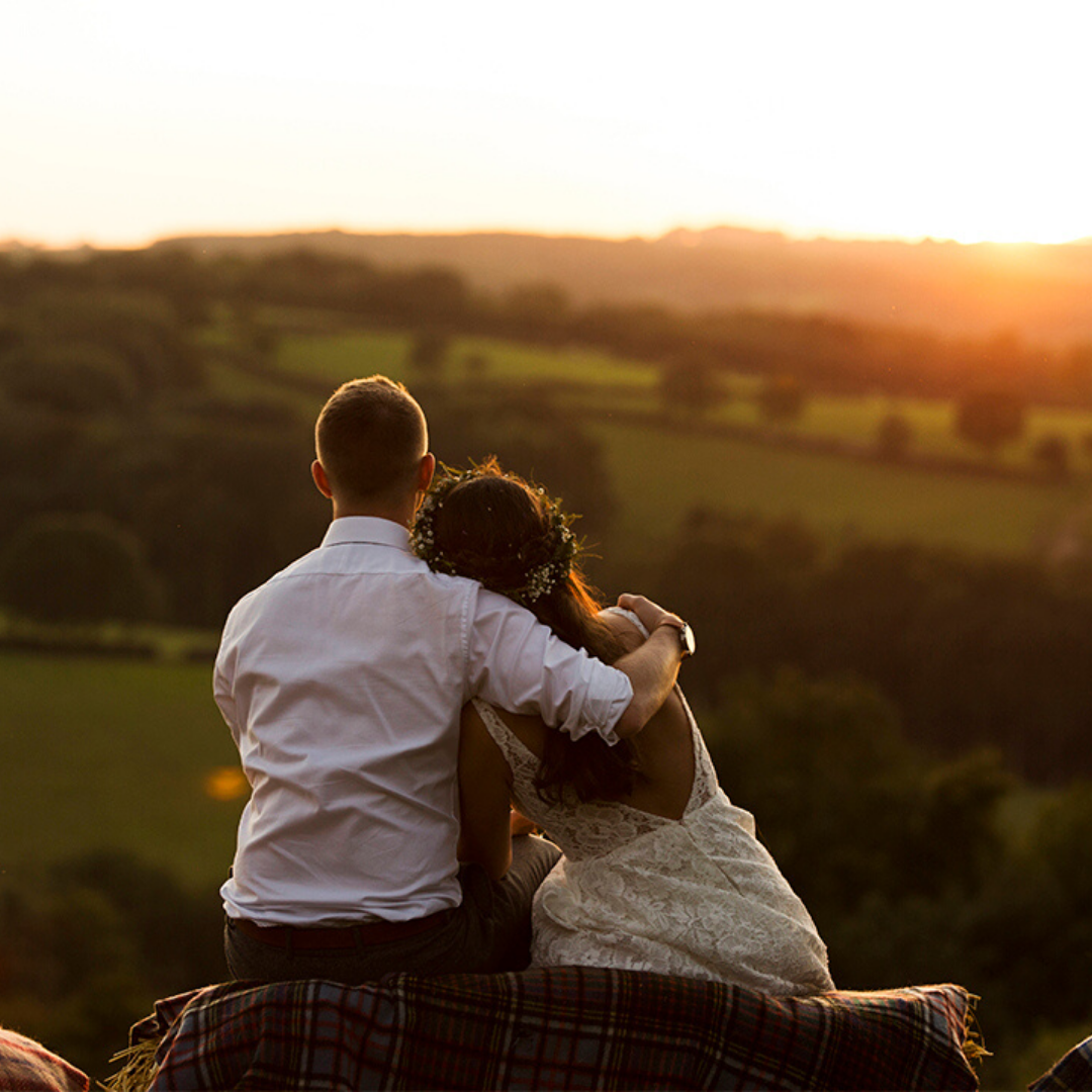 Happy couple at country ways, enjoying the sunset view