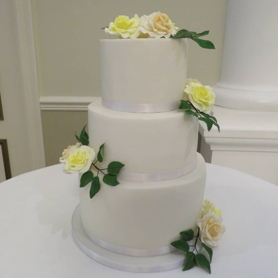 Three tier fondant wedding cake with yellow and peach handmade sugar roses