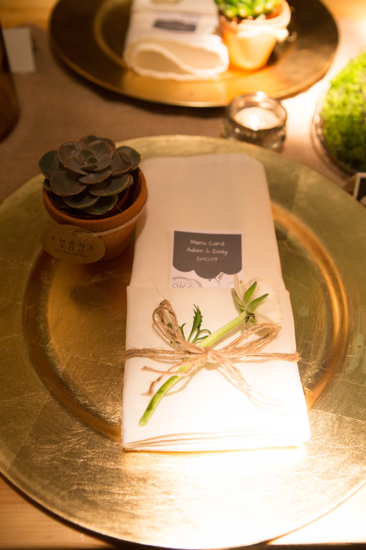 Gold charger plate with white napkin and greenery and succulent favour