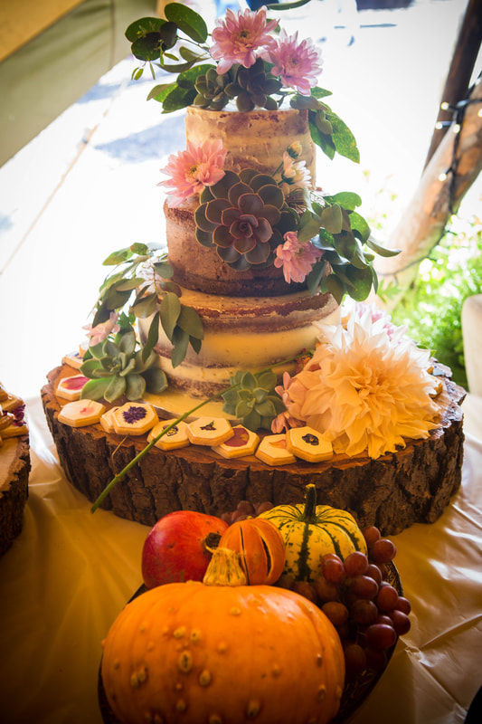 Rustic semi naked wedding cake with fresh flower cascade