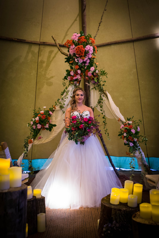 Bride under v arch with pink bouquet