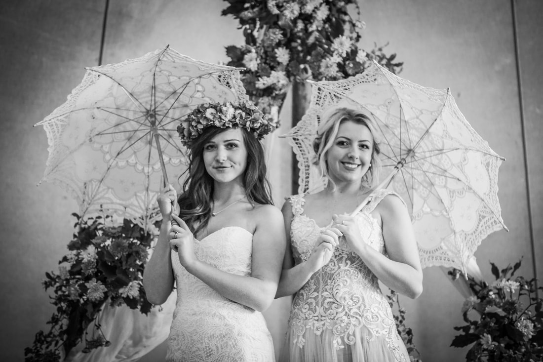 Two brides with lace umbrellas in black & white
