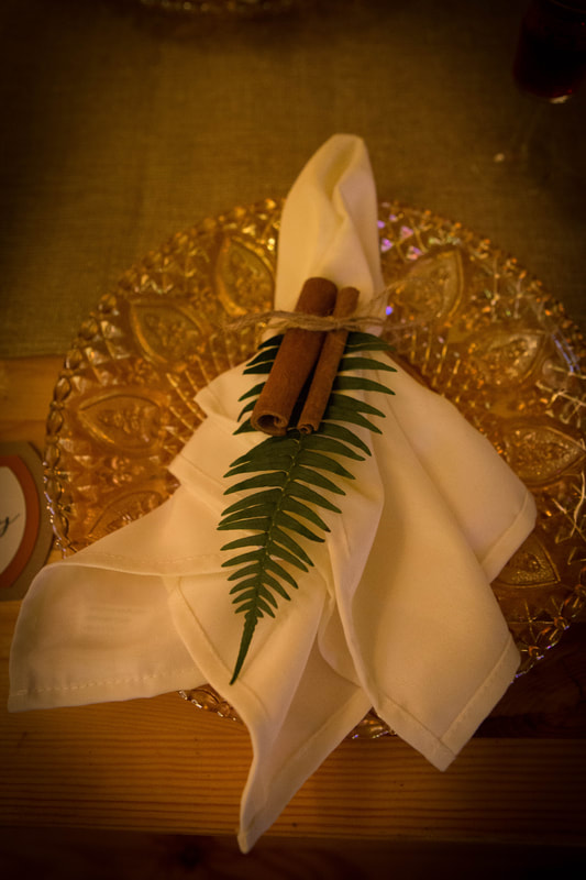 Gold charger plates with white napkin, cinnamon sticks and fern