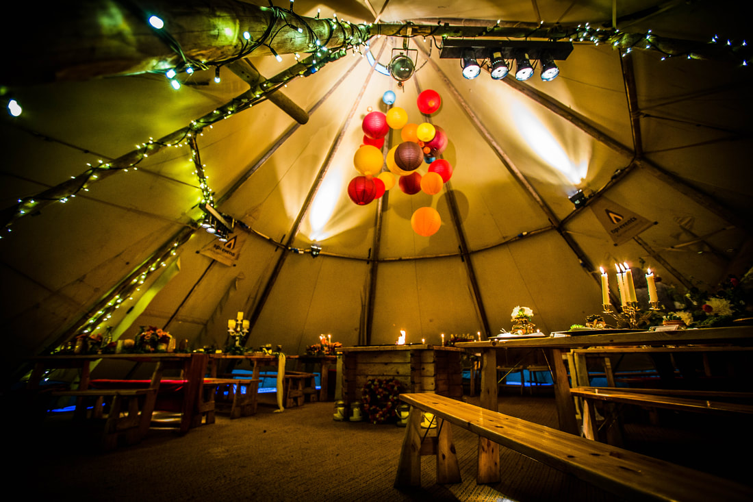 Side view of tipi with tables and lanterns setup